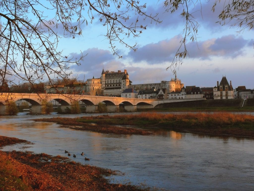 Chateau Royal d'Amboise seen from across the Loire River with the bridge leading to town in the foreground.