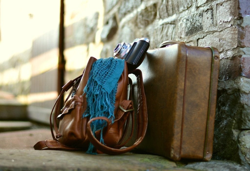 brown leather luggage with turquoise pashmina draped over a bag