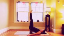 Woman in viparita karani with two blocks under the sacrum and legs straight in the air (yoga pose)