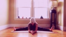 Woman in seated straddle forward fold (yoga pose)