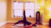 Woman in supported bridge variation with one leg lifted to sky, the other leg straight down with the foot on the floor (yoga pose)