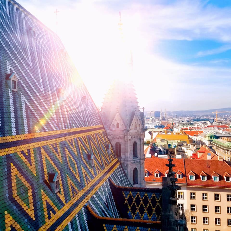 Colorful rooftop of St. Stephen's Cathedral in Vienna with a bright sun glare reflecting