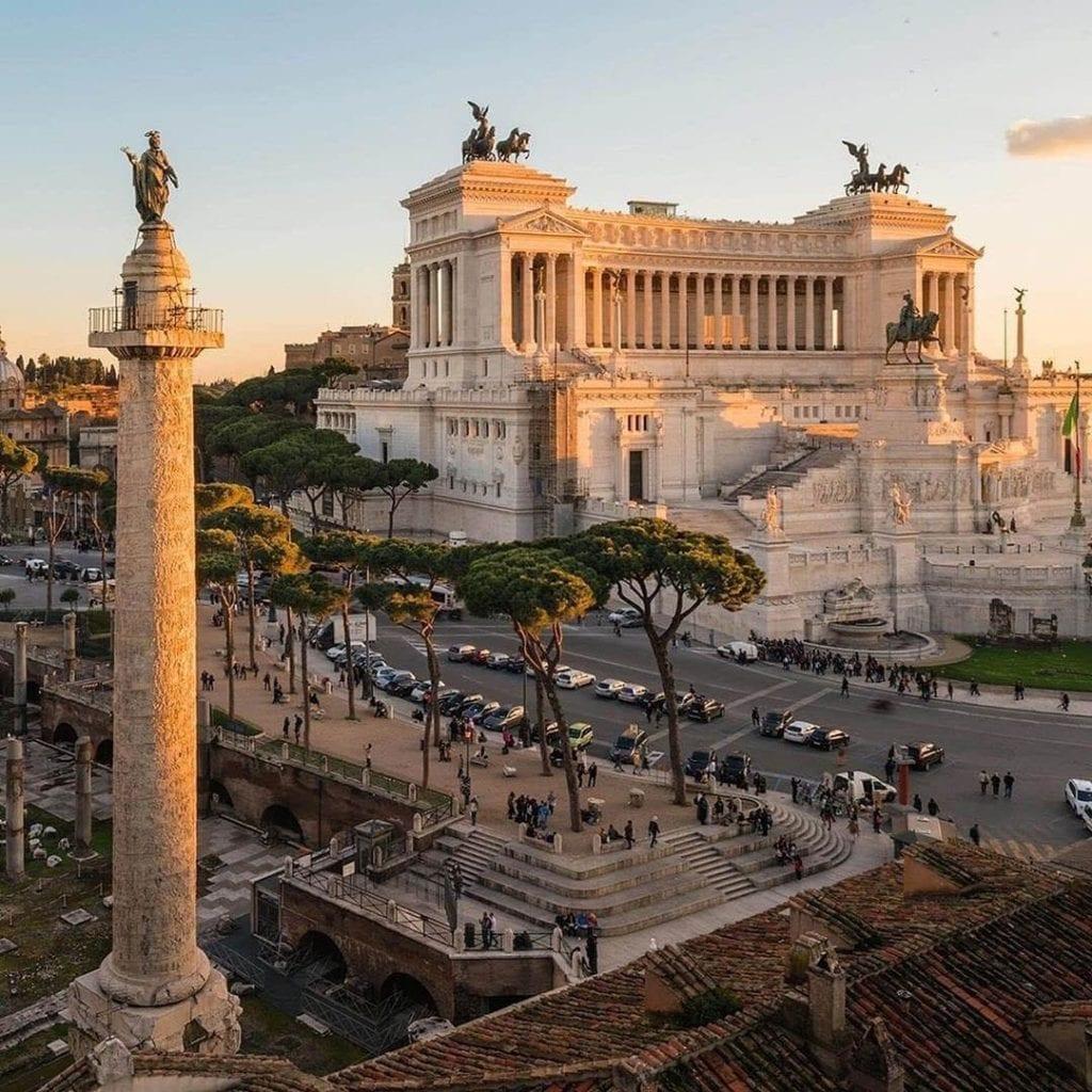 Trees, crowds, and ancient Roman architecture in the Italian capital city of Rome at Altare della Patria.