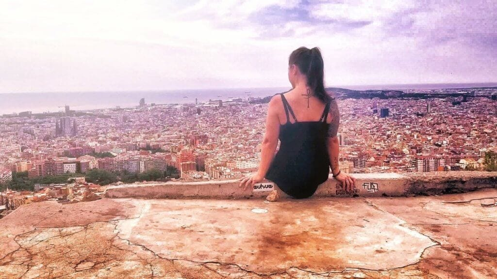 woman sitting on the bunkers del carmel in barcelona overlooking the city for one of the most beautiful places in barcelona