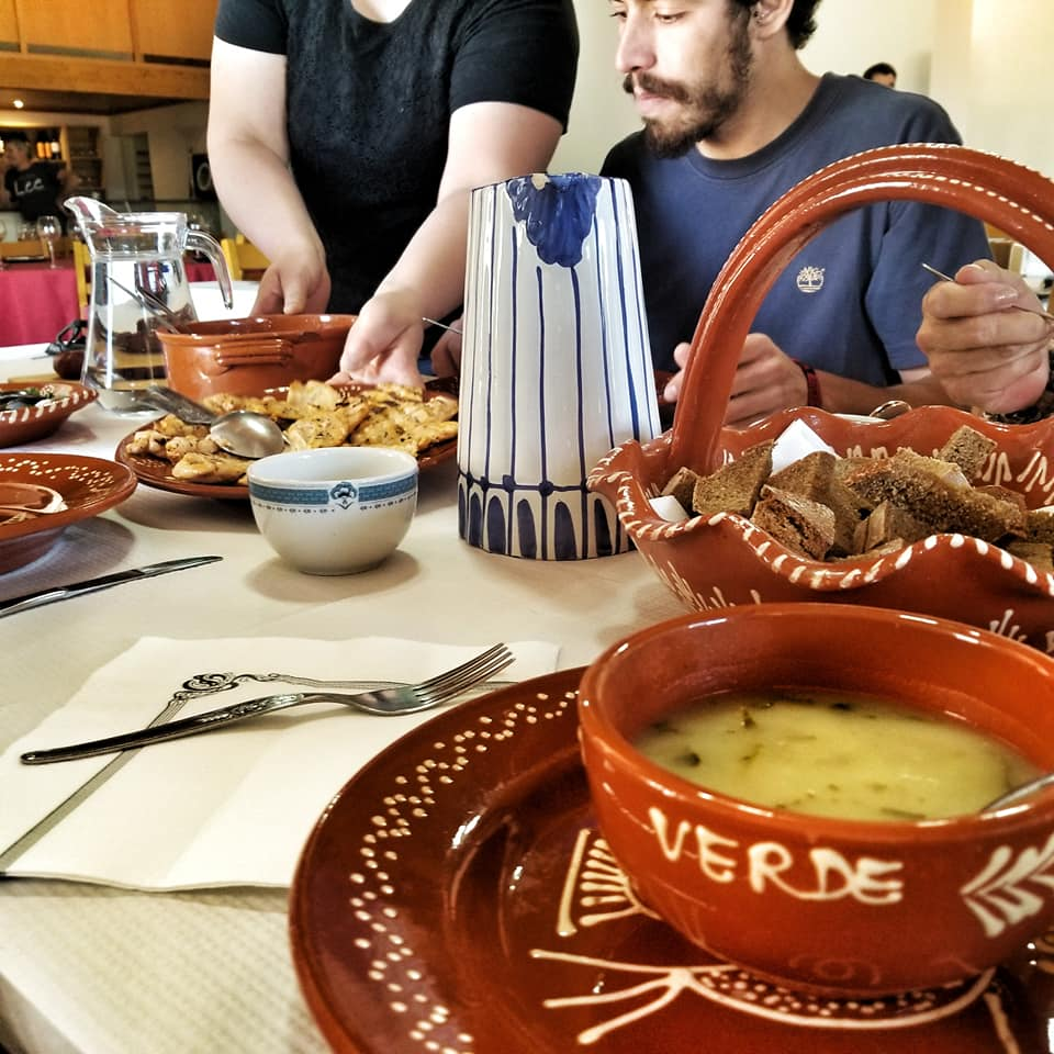 Caldo Verde and other Portuguese foods at a large table.