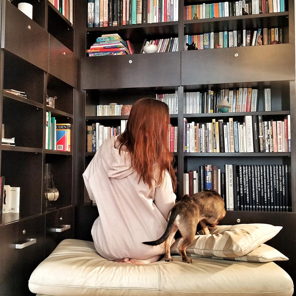 Woman and dog facing away from camera toward a giant bookcase.