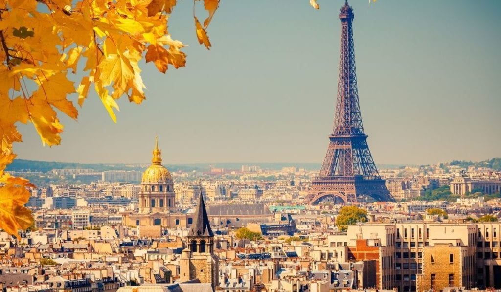 View of the Eiffel Tower through yellow autumn leaves from far across the city of Paris.