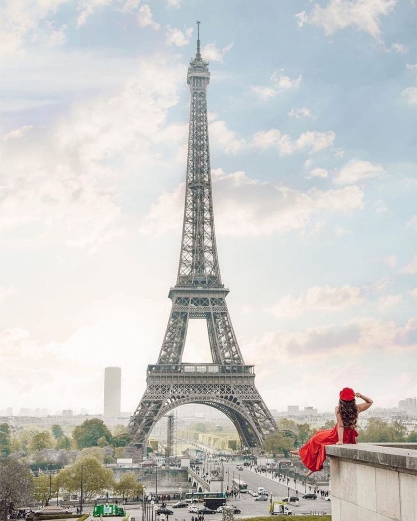 Woman sitting on a stone wall at Trocadero looking at the Eiffel Tower.