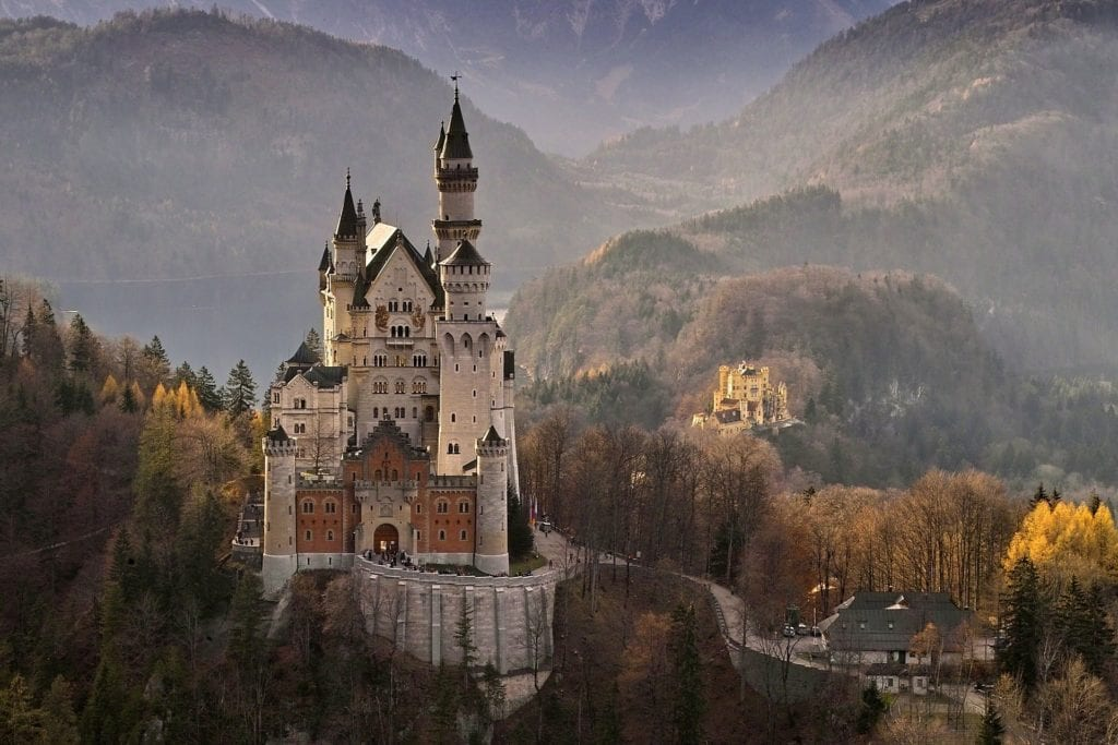 Dreamy Neuschwanstein Castle in Germany, seen from afar with autumn trees in the background.