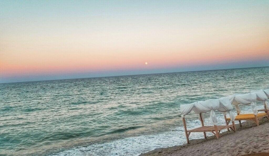 Moonrise over empty beach in Vama Veche, Romania with empty cabanas