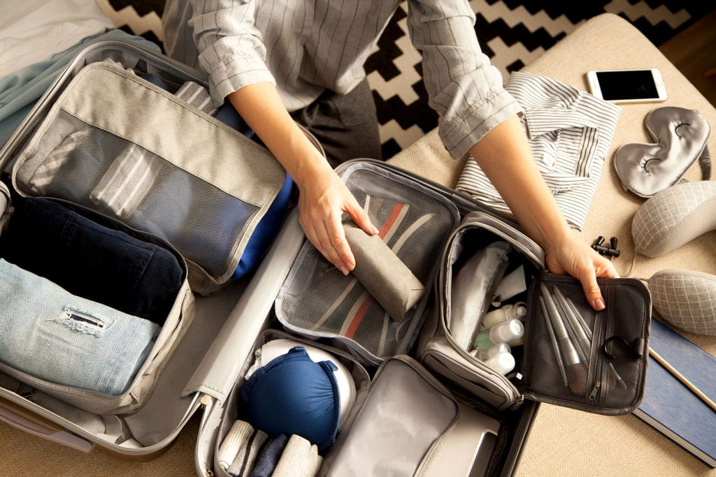 Woman packing a suitcase in packing cubes.