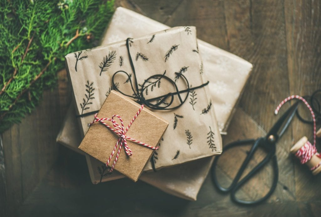 Christmas gifts wrapped on a wooden floor next to scissors and evergreens.