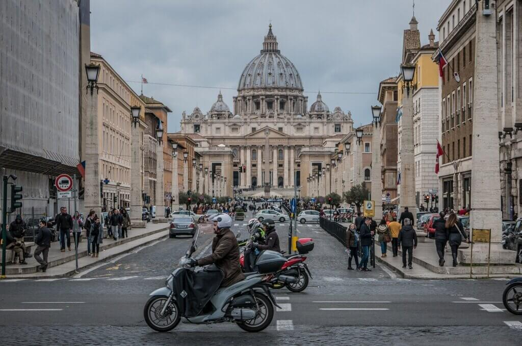 Traffic and pedestrians in front of St. Peter's Basilica in Vatican City.