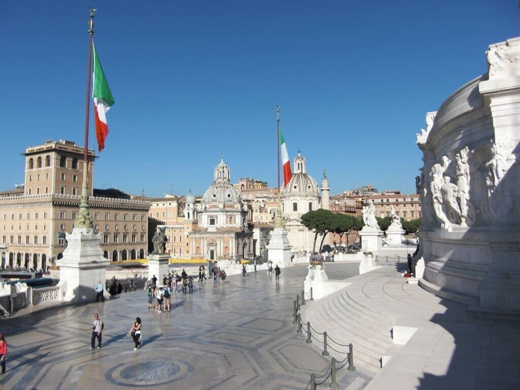 Vittorio Emmanuele in Rome, Italy.  Italian flags hanging high and people walking around the terrace.