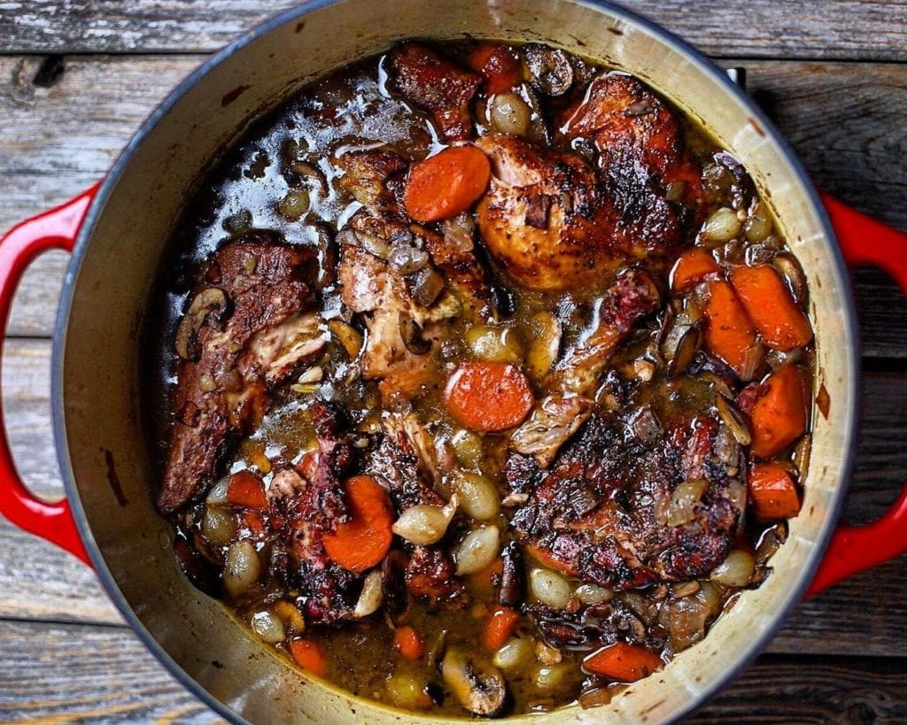 Red pot of coq-au-vin on a wooden table, a traditionally French dish to eat.