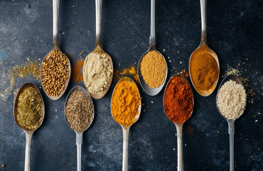 Spoons arranged opposite each other on a black table filled with different colored spices.