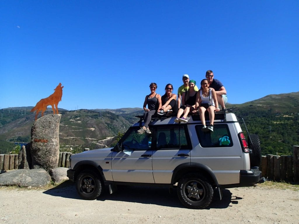 Six people sitting on the roof of a 4x4 in the mountains of Peneda-Geres day trip from Porto
