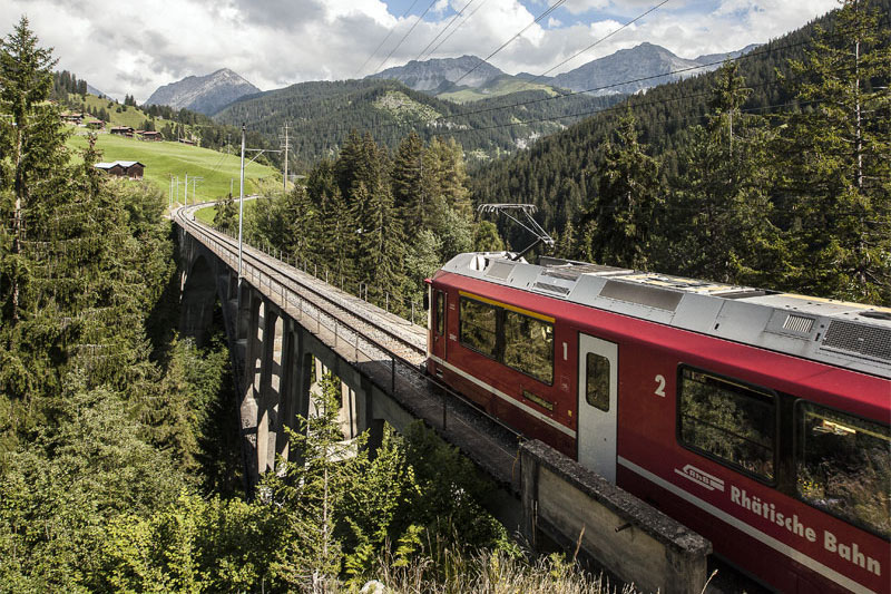 Chur to Arosa rail line on an elevated track through wooded mountains.