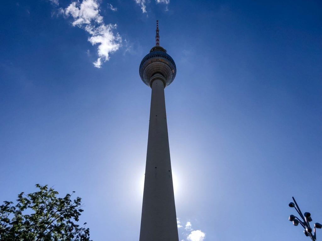 Berlin TV Tower as seen from right below and looking up with the sun blocked by the tower and shining from behind.