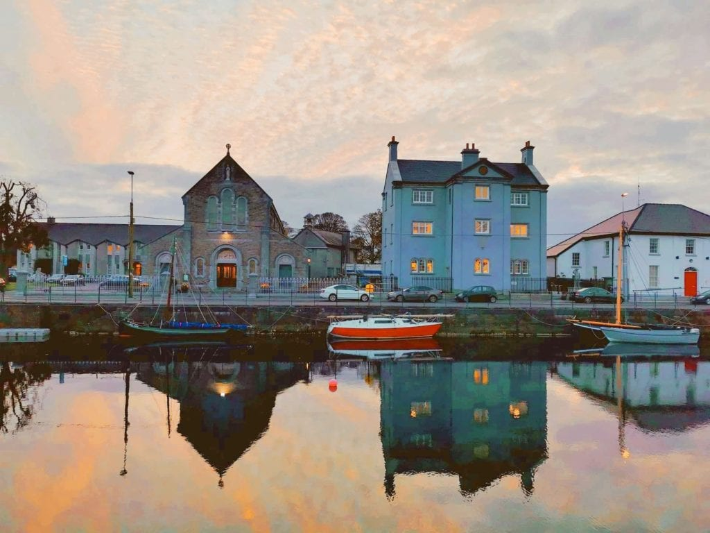 Buildings in Galway bay reflected on the water below during sunset.
