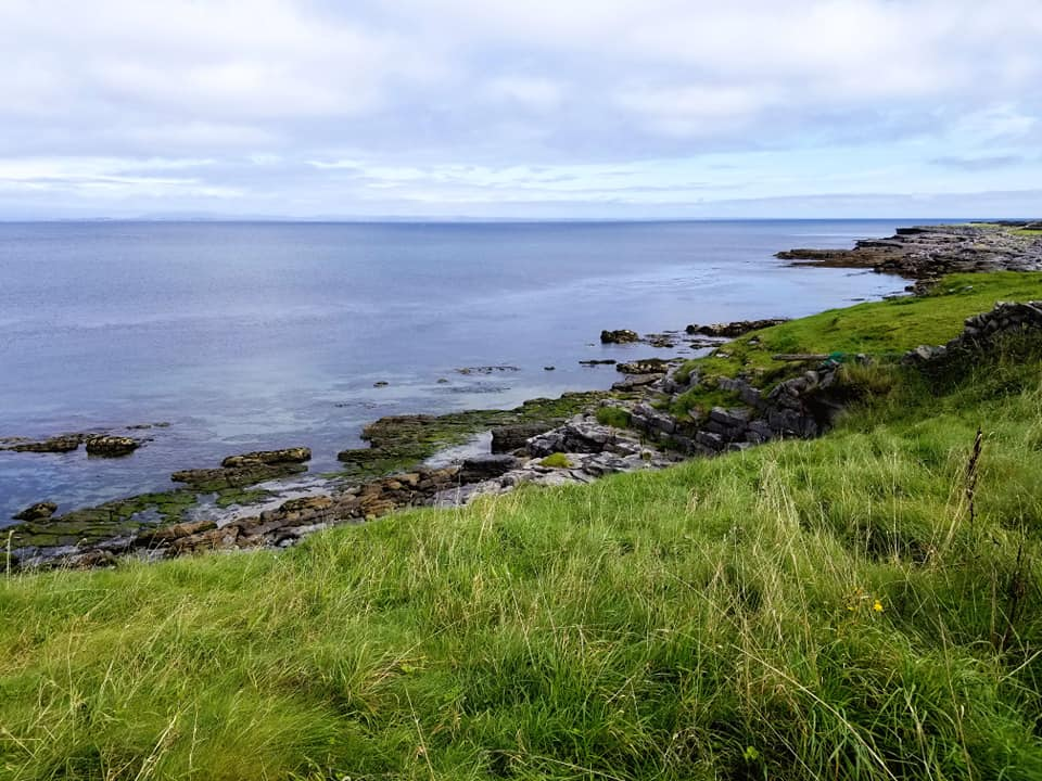 Coastal views from the island of Inis Mor with sea grass, rocky cliffs and blue ocean.