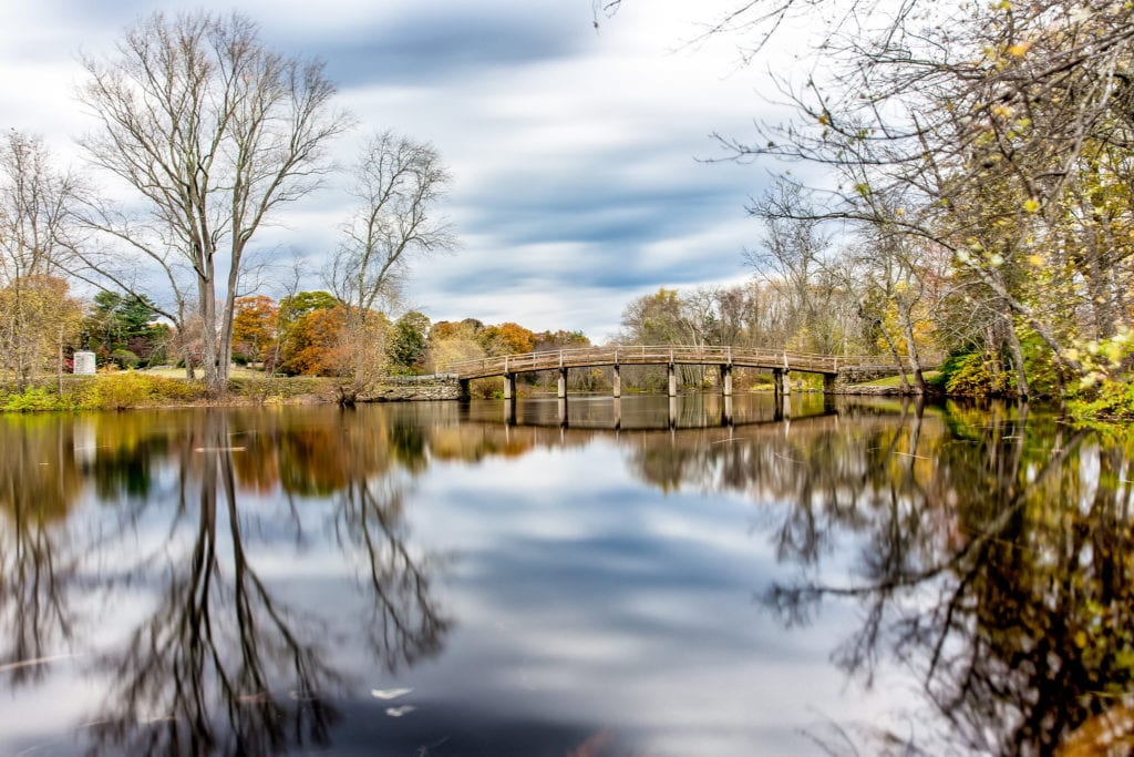 Old North Bridge in Concord, Mass, a great day trip from Boston.  The bridge is reflected in the water like a mirror and the leaves are beginning to turn green with spring.