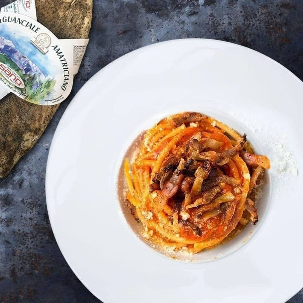 Bowl of bucatini all'amatriciana, a traditional Italian dish. Next to a slab of guanciale.
