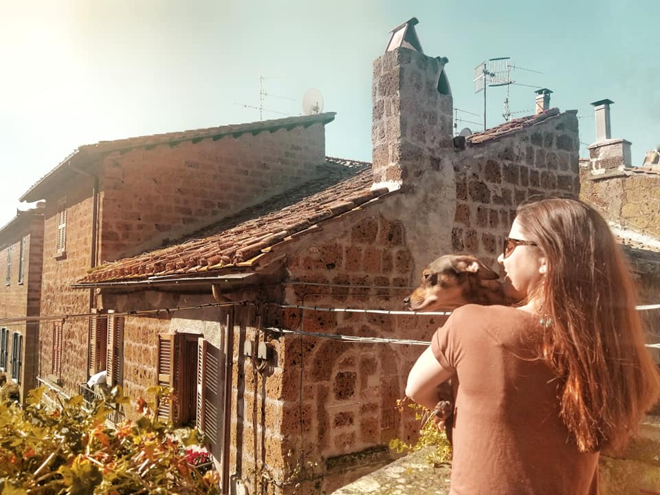 Woman and dog looking over an Italian medieval village from a high-up loggia.