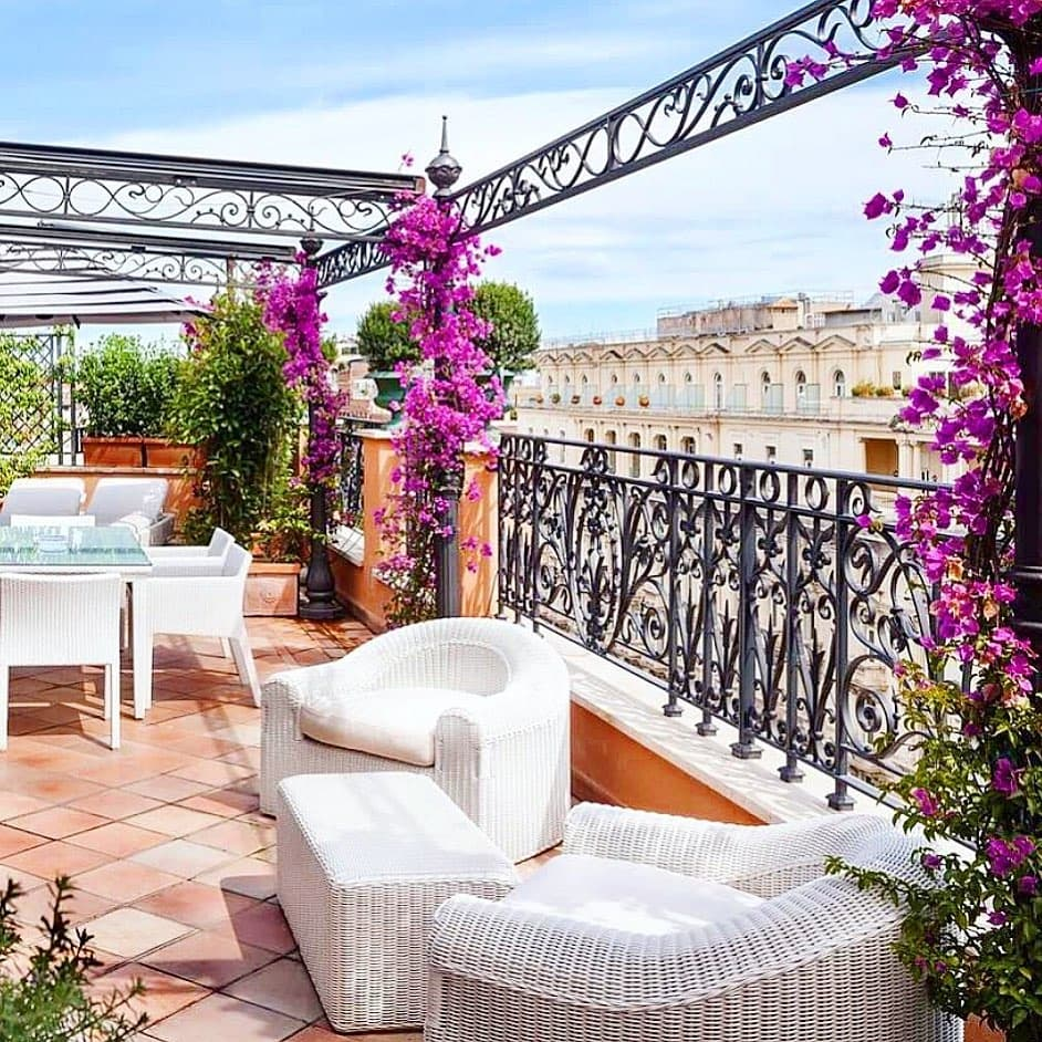 Rooftop terrace at Baglioni Hotel Regina, a luxury hotel in Rome.  There are purple flowers covering the iron gates.