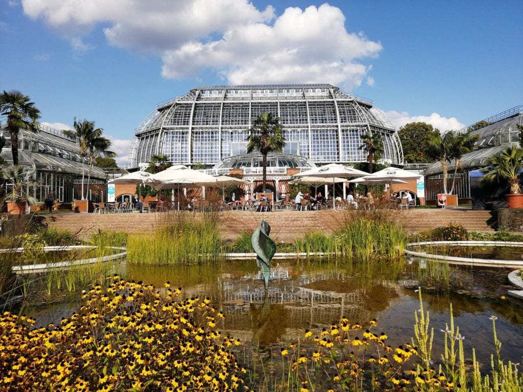 Outside of the Botanical Garden Berlin with cafe tables and a small pond in front of the greenhouse.