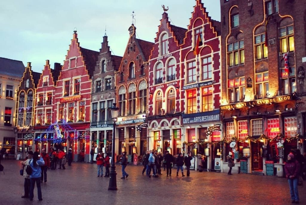 Bruges Market Hall in the evening with many people walking around, a great historic landmark in Bruges.