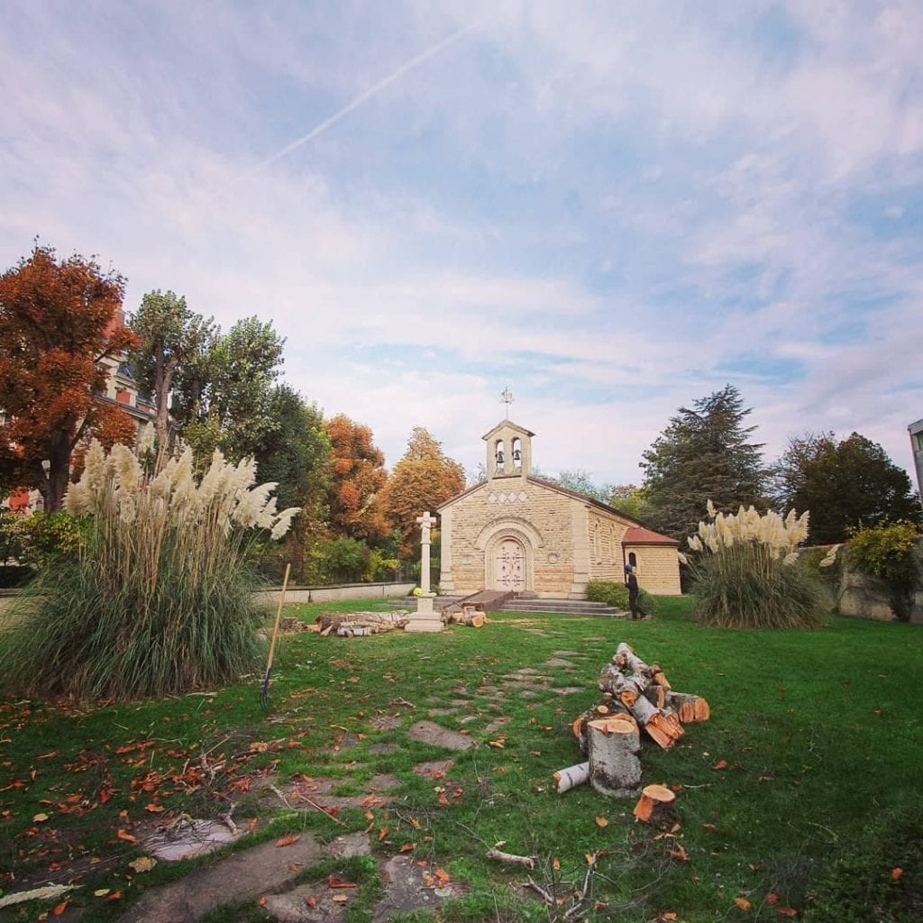 Small chapel surrounded by many tees and landscaped gardens in Reims, France.
