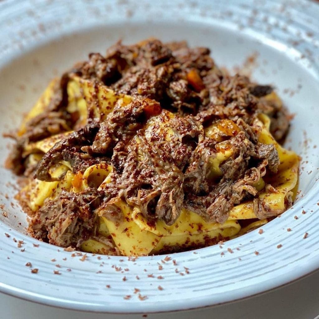 Dish of wild boar over pappardelle pasta