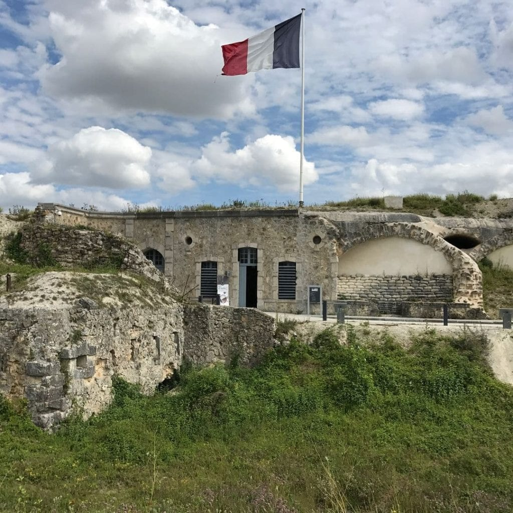Outside of Forte de la Pampelle, with long grass and a French flag flying high.