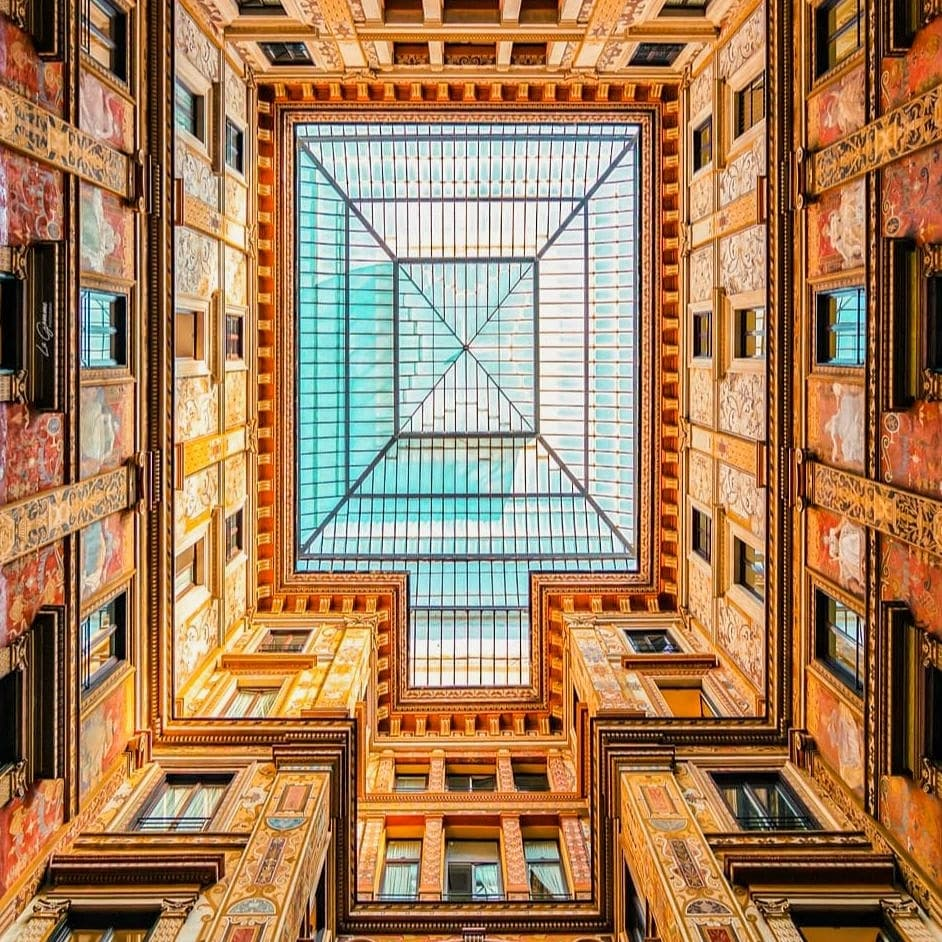 Glass and iron ceiling of Galleria Sciarra in Rome, Italy, edited in hues of orange and teal.  One of the most beautiful places in Rome.