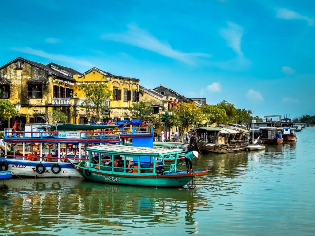 Boats along Hoi An in vietnam with yellow buildings and blue skies.