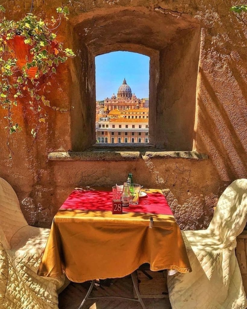 Small table set outdoors with a small window overlooking St. Peter's Basilica at the Hotel de Russie in Rome, Italy.