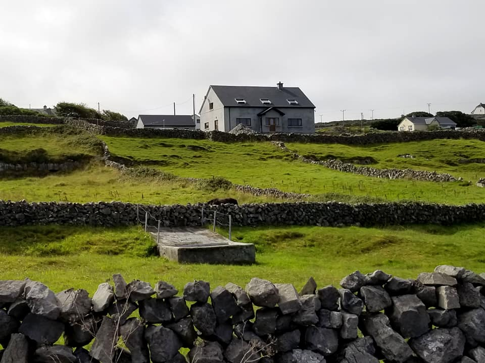 White country house on the hills of Inis Mor with green grass and stone walls covering the landscape.