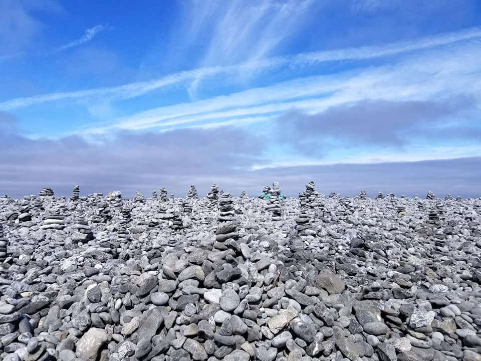 Rock piles that people have formed on the island of Inis Mor with crisp blue skies and whispy clouds.