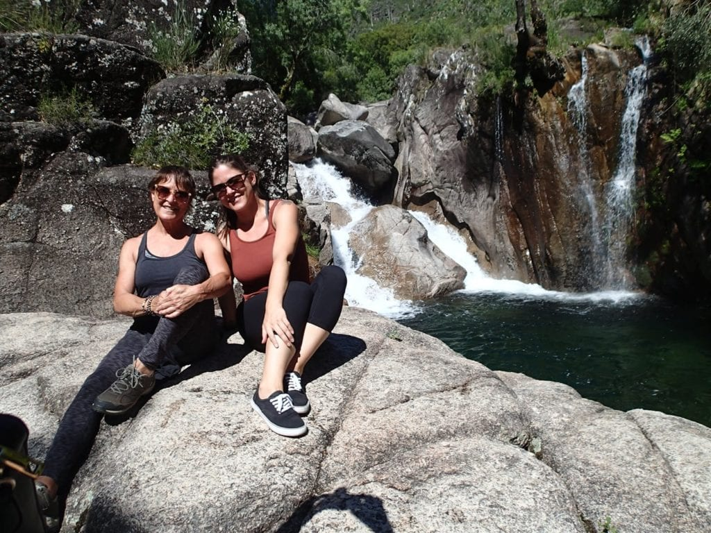 Two women sitting on a rock in front of a blue swimming hole in Peneda-Geres, Portugal