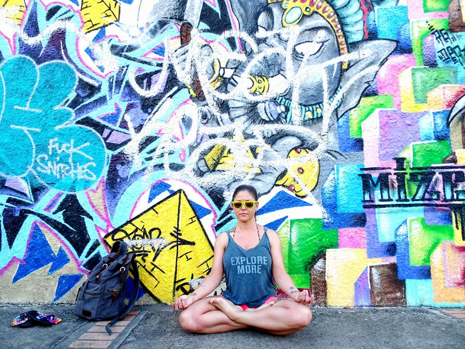 Woman seated in lotus pose on a sidewalk in front of colorful graffiti with Ganesh painted in background.