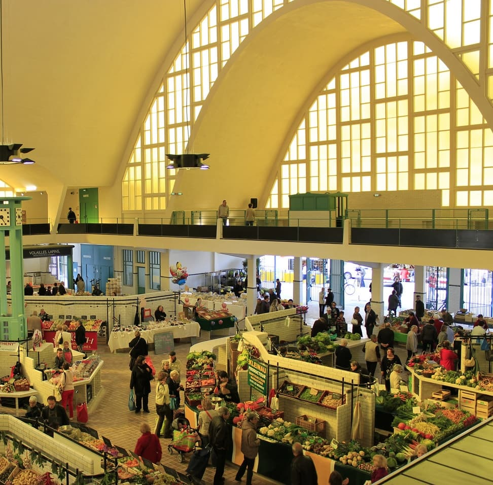 Many shoppers at the covered market doing their grocery shopping in Reims, France.