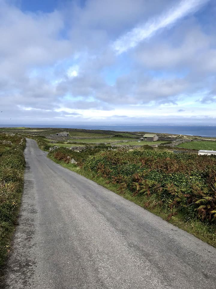 Long, empty road on the island of Inis Mor surrounded by grassy fields and coastline.