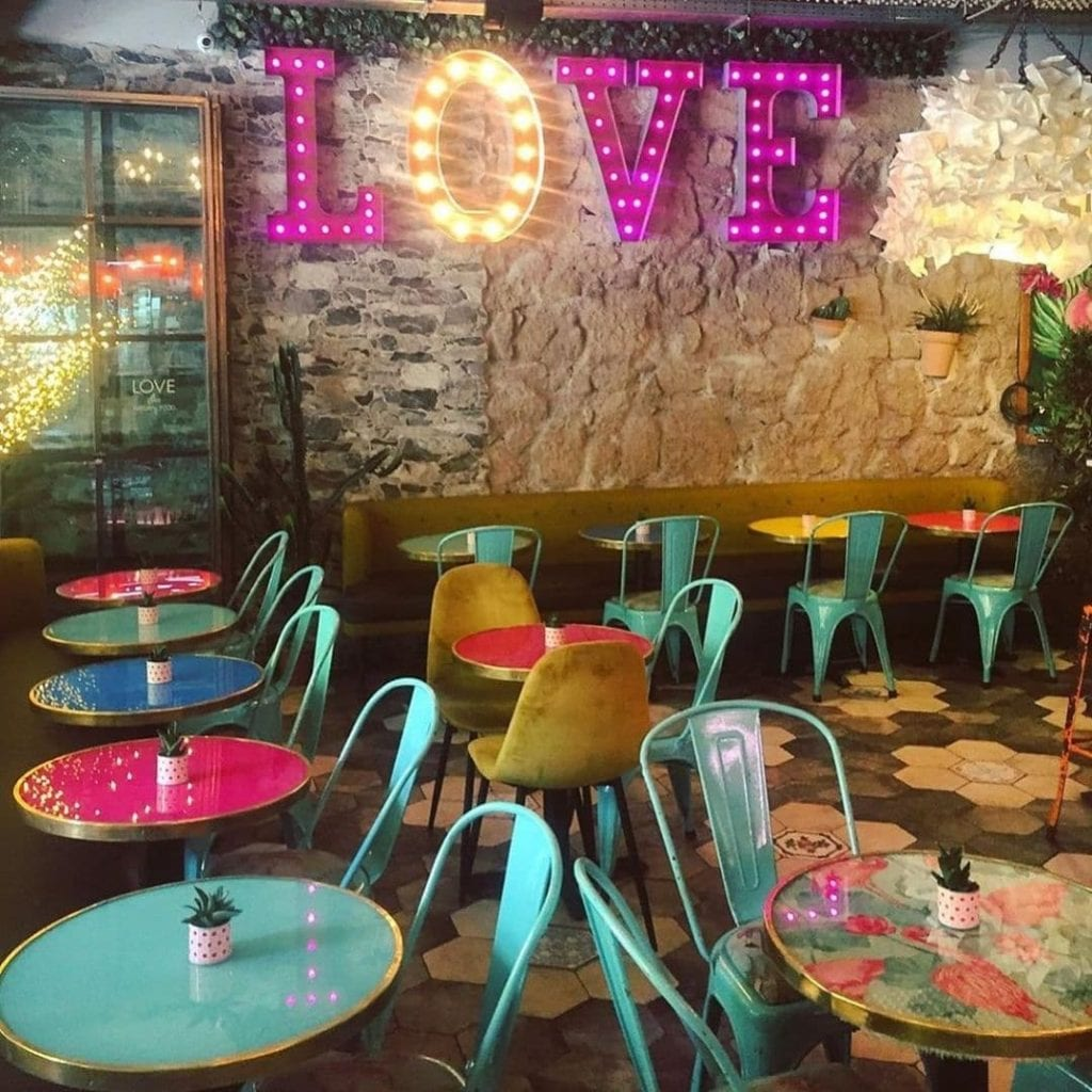 Interior of Love Natural Food in Rome, Italy with brightly colored tables and chairs and the words illuminated 'LOVE' on the wall.