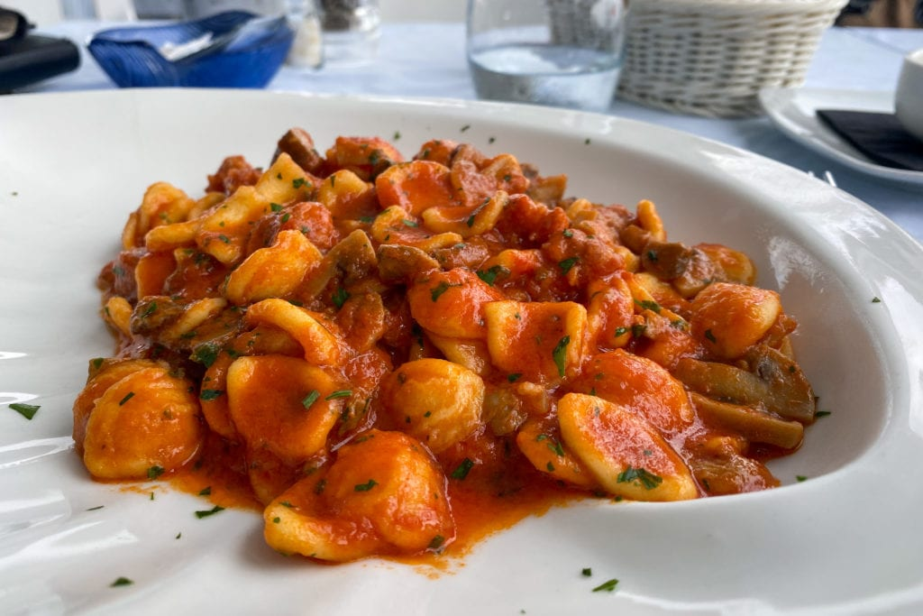 A plate of orecchiette in a hearty tomato sauce with mushrooms and chopped parsley.
