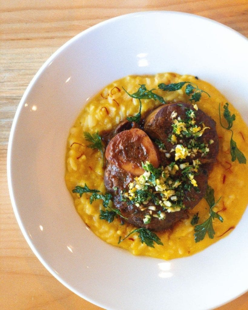Veal shanks surrounded by a plate of saffron risotto and topped with gremolata.