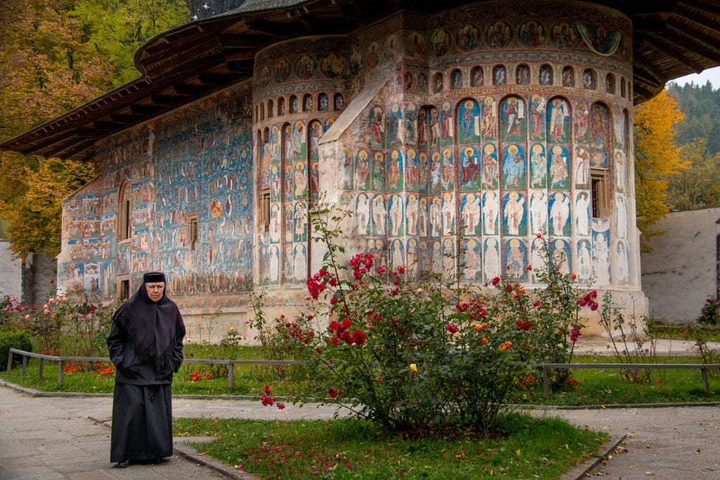 Woman dressed in black outside one of the painted monasteries in Bucovina, Romania.