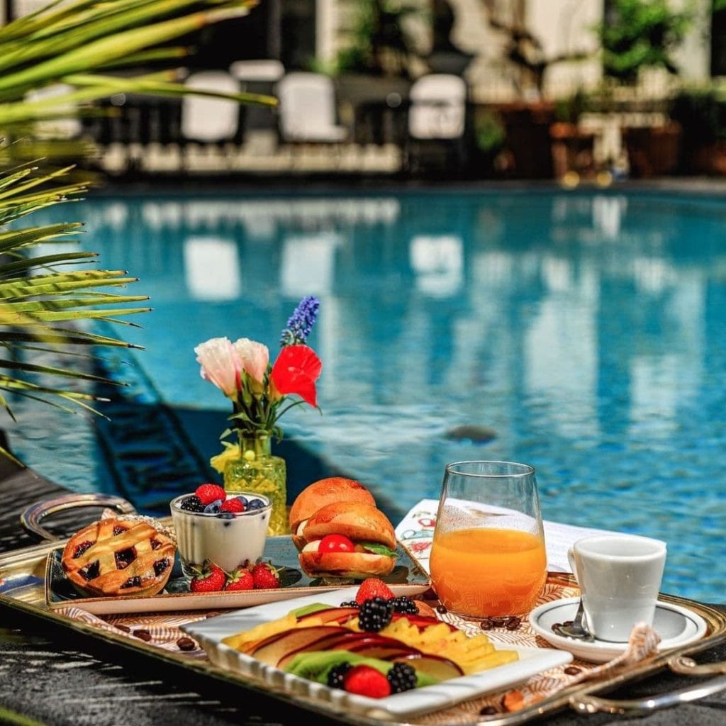 Breakfast tray with fresh fruits, croissants, yogurt, juice and coffee outside the pool at Palazzo Dama.