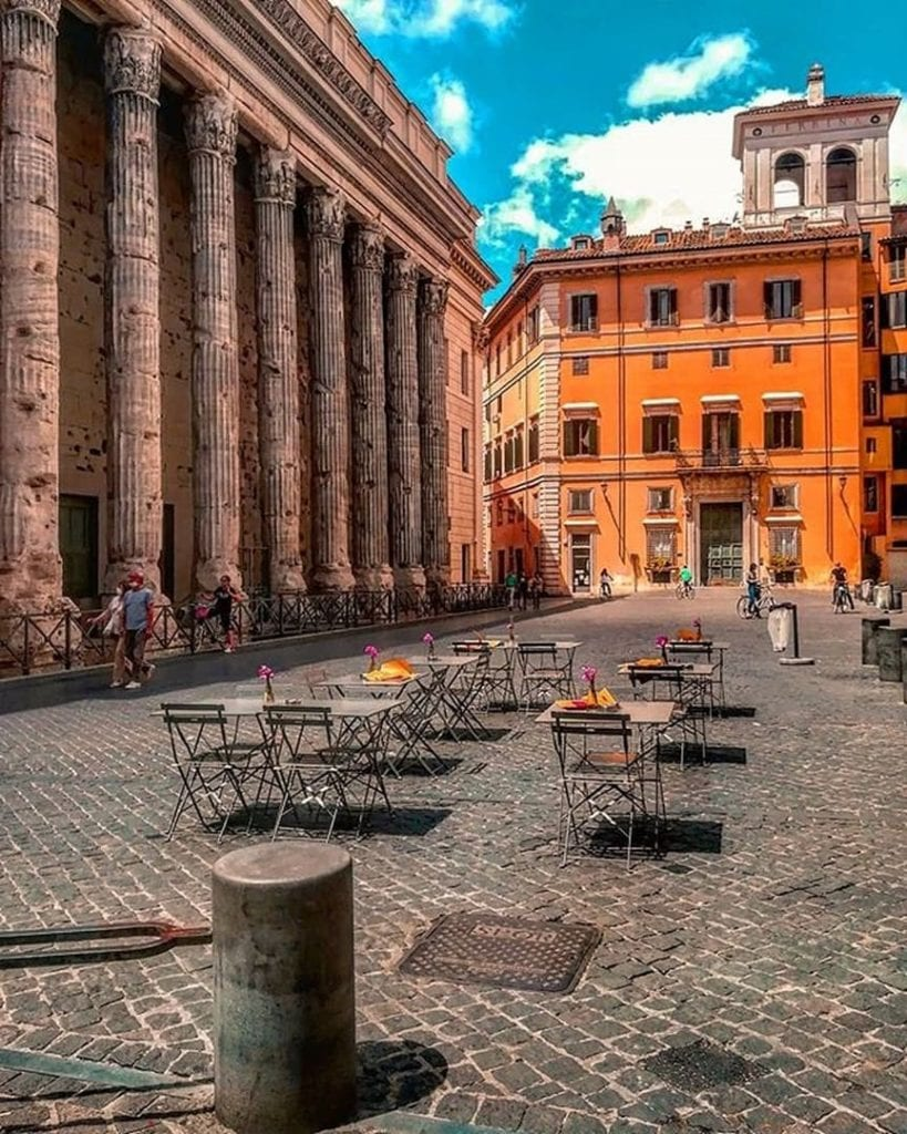 Empty tables set up in Piazza di Pietra with tall ancient columns on the left hand side of the image.