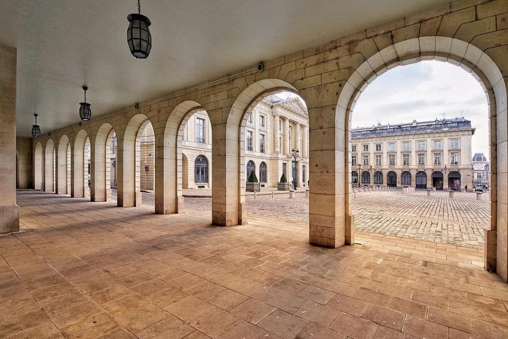 Looking into a large square from the arched arcade at Place Royale in Reims, France.